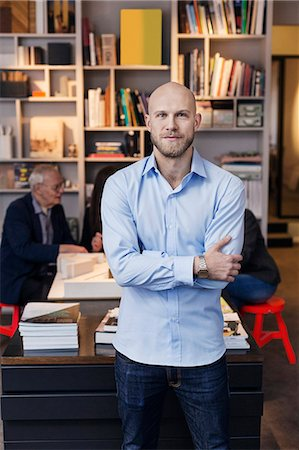 people - Portrait of confident businessman standing arms crossed while colleagues working in background at office Stock Photo - Premium Royalty-Free, Code: 698-08226313