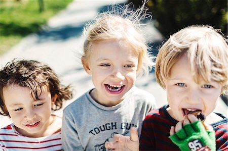 Portrait of happy boy eating ice cream while walking with friends at yard Stock Photo - Premium Royalty-Free, Code: 698-08226336