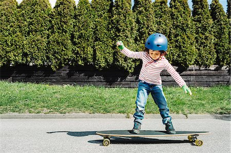 Full length of boy balancing on skateboard at yard Stock Photo - Premium Royalty-Free, Code: 698-08226346