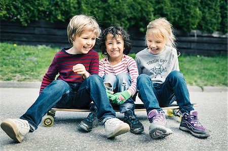 Playful friends sitting on skateboard at yard Stock Photo - Premium Royalty-Free, Code: 698-08226356