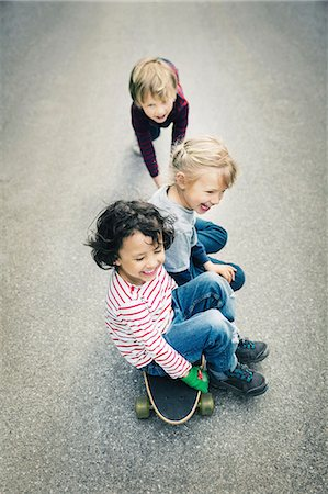 High angle view of children enjoying while sitting on skateboard Stock Photo - Premium Royalty-Free, Code: 698-08226350