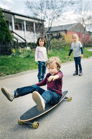 Children looking at friend skateboard on footpath outside house Stock Photo - Premium Royalty-Free, Code: 698-08226352