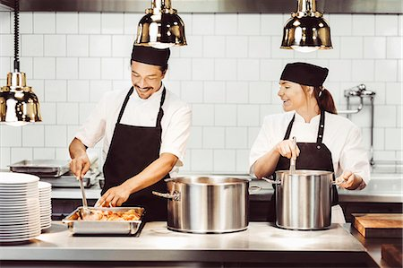 restaurant - Happy male and female chefs preparing food at kitchen counter Stock Photo - Premium Royalty-Free, Code: 698-08226371