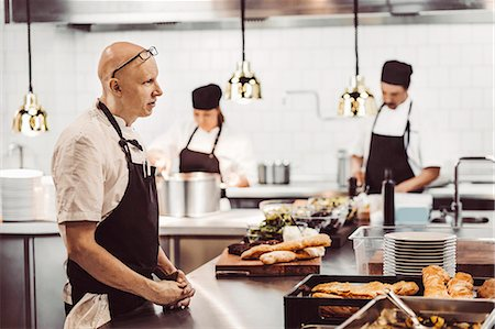 Side view of male chef standing at kitchen counter with colleagues working in background Stock Photo - Premium Royalty-Free, Code: 698-08226380