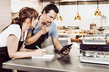 Male and female chefs using digital tablet while writing recipe at commercial kitchen counter Stock Photo - Premium Royalty-Free, Code: 698-08226401