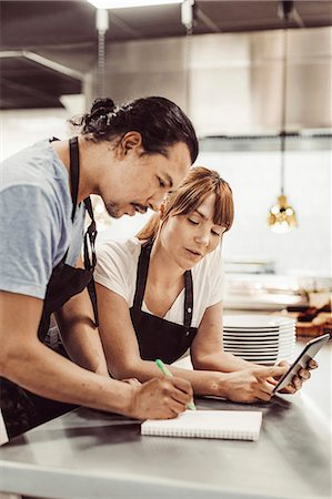 small business - Chefs using digital tablet while writing recipe at commercial kitchen counter Stock Photo - Premium Royalty-Free, Code: 698-08226402