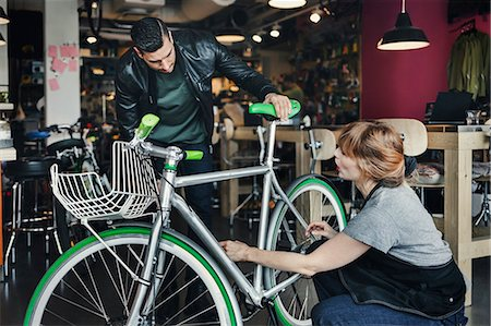 shop - Female mechanic analyzing bicycle while talking to customer in repair shop Stock Photo - Premium Royalty-Free, Code: 698-08226416