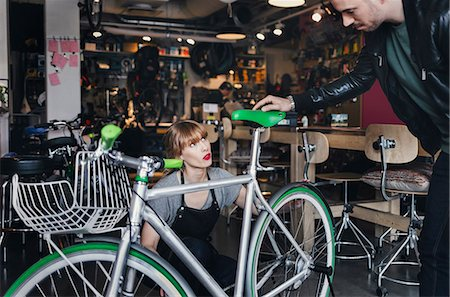 shop - Female mechanic analyzing bicycle while talking to male customer in repair shop Stock Photo - Premium Royalty-Free, Code: 698-08226417