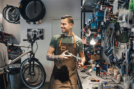 stockholm - Smiling male mechanic looking at colleague while repairing pedal in workshop Stock Photo - Premium Royalty-Free, Code: 698-08226435