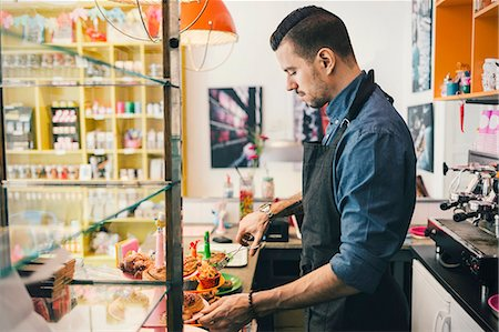 european cafe bar - Side view of male barista using tongs to remove cupcake at cafe counter Stock Photo - Premium Royalty-Free, Code: 698-08226452