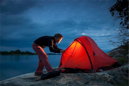 Woman looking into tent at lakeshore during dusk Stock Photo - Premium Royalty-Free, Code: 698-08226494