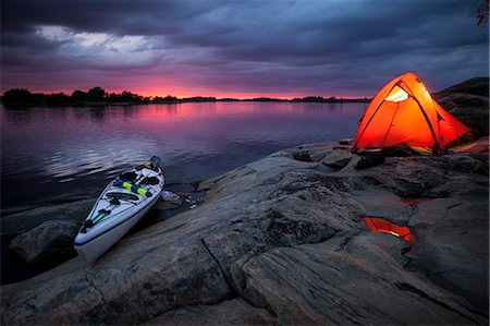 Tent and kayak at lakeshore during sunset Stock Photo - Premium Royalty-Free, Code: 698-08226497
