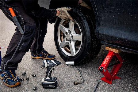 Low section of mechanic changing car tire on street Stock Photo - Premium Royalty-Free, Code: 698-08226491