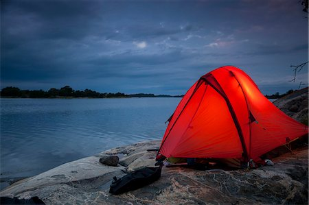 Tent on rock at lakeshore during dusk Stock Photo - Premium Royalty-Free, Code: 698-08226492
