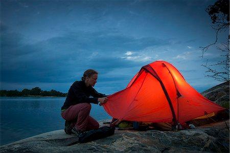 Woman fixing tent at lakeshore during dusk Stock Photo - Premium Royalty-Free, Code: 698-08226493