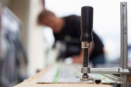 Clamp on wooden plank with female carpenter working in background Stock Photo - Premium Royalty-Free, Code: 698-08226504