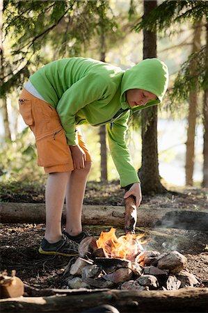 Boy igniting campfire at lakeshore Stock Photo - Premium Royalty-Free, Code: 698-08226511