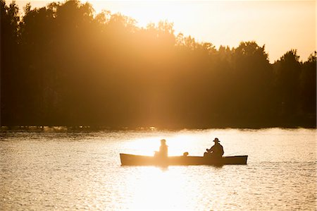 Silhouette father and son traveling in canoe on lake during sunset Stock Photo - Premium Royalty-Free, Code: 698-08226512