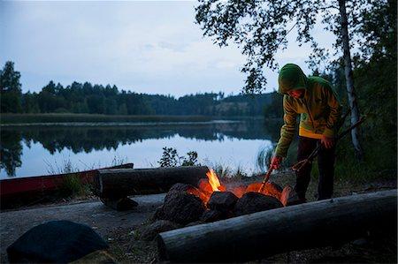 Boy igniting campfire at lakeshore during dusk Stock Photo - Premium Royalty-Free, Code: 698-08226525