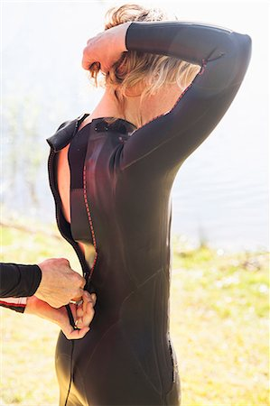 Cropped hands of man fastening woman's wetsuit at lakeshore Stock Photo - Premium Royalty-Free, Code: 698-08226522
