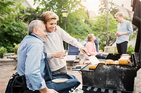 father and son barbecuing at yard Stock Photo - Premium Royalty-Free, Code: 698-08226547