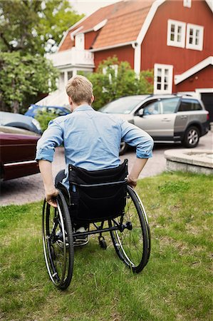 Rear view of man in wheelchair at yard Stock Photo - Premium Royalty-Free, Code: 698-08226542