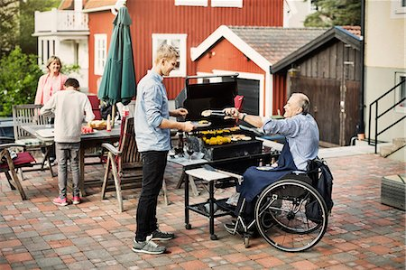 Disabled man serving barbecued food to son at yard Stock Photo - Premium Royalty-Free, Code: 698-08226552