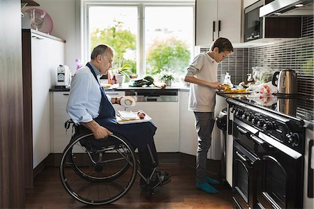 Son with disabled father cutting vegetables in kitchen Stock Photo - Premium Royalty-Free, Code: 698-08226576