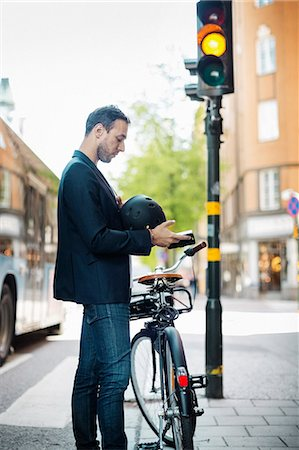 Side view of businessman using mobile phone while standing with bicycle on city street Stock Photo - Premium Royalty-Free, Code: 698-08226609