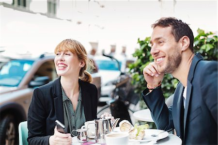 Happy business commuters looking away while sitting at sidewalk cafe Stock Photo - Premium Royalty-Free, Code: 698-08226603