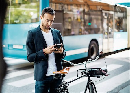 Businessman using mobile phone while standing with bicycle on city street Stock Photo - Premium Royalty-Free, Code: 698-08226610
