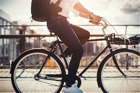 Low section of businessman riding bicycle on bridge Stock Photo - Premium Royalty-Free, Code: 698-08226636