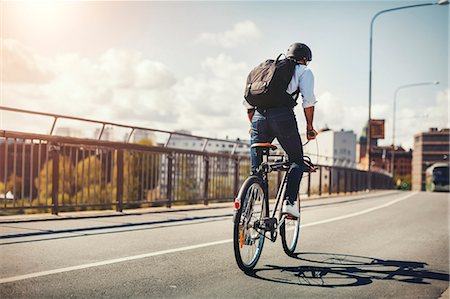 Rear view of businessman riding bicycle on bridge in city Stock Photo - Premium Royalty-Free, Code: 698-08226638