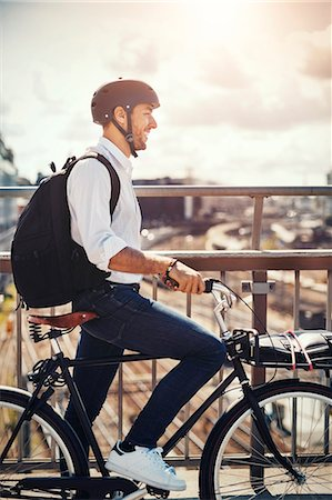 Smiling businessman with bicycle looking at city view while standing on bridge Stock Photo - Premium Royalty-Free, Code: 698-08226633