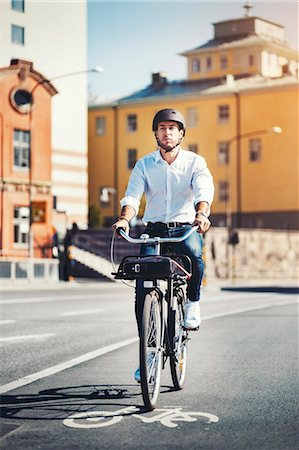 Businessman commuting on bicycle in city Stock Photo - Premium Royalty-Free, Code: 698-08226643