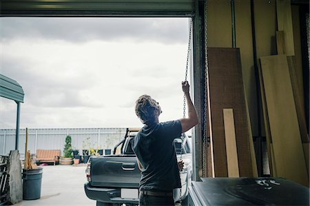 Rear view of carpenter pulling shutter at entrance of workshop Stock Photo - Premium Royalty-Free, Code: 698-08226651