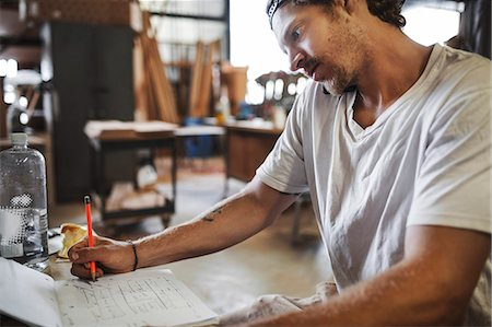 Carpenter using mobile phone while reading document in workshop Stock Photo - Premium Royalty-Free, Code: 698-08226676