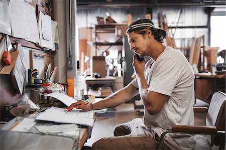 Side view of carpenter using mobile phone while reading document in workshop Stock Photo - Premium Royalty-Free, Code: 698-08226677