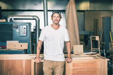 Portrait of confident carpenter leaning on cabinet in workshop Stock Photo - Premium Royalty-Free, Code: 698-08226688