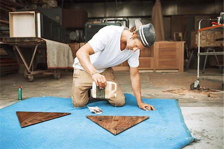 Carpenter pouring oil on triangle shaped wood at workshop Stock Photo - Premium Royalty-Free, Code: 698-08226694