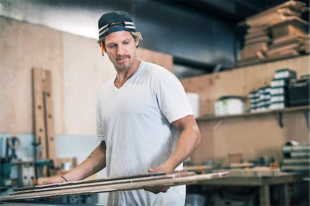 Carpenter looking at wooden planks in workshop Stock Photo - Premium Royalty-Free, Code: 698-08226690