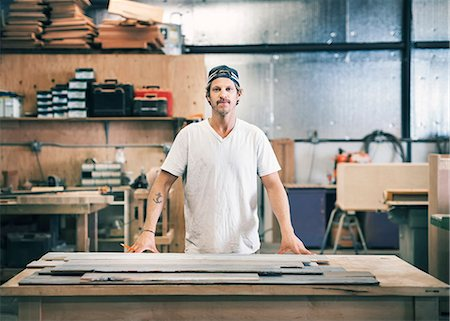 Portrait of confident carpenter standing at workbench in workshop Stock Photo - Premium Royalty-Free, Code: 698-08226693