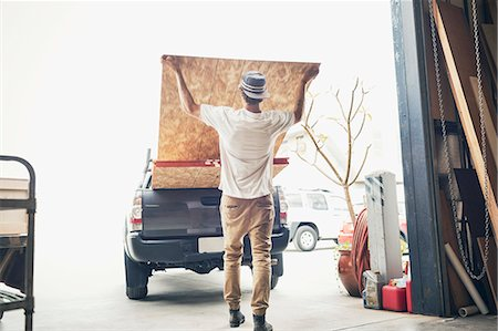 Rear view of man loading wooden planks in pick-up truck Stock Photo - Premium Royalty-Free, Code: 698-08226716