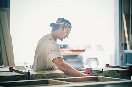 Side view of carpenter making furniture in factory Stock Photo - Premium Royalty-Free, Code: 698-08226717