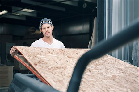Carpenter loading wooden planks in pick-up truck Stock Photo - Premium Royalty-Free, Code: 698-08226710