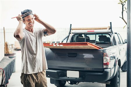Happy carpenter standing by pick-up truck outside workshop Stock Photo - Premium Royalty-Free, Code: 698-08226711