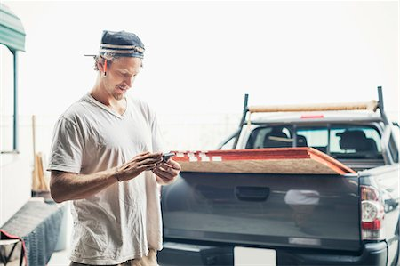 Carpenter using mobile phone by pick-up truck against clear sky Stock Photo - Premium Royalty-Free, Code: 698-08226712