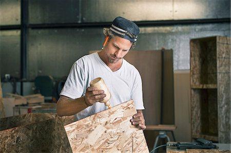 Carpenter applying glue on wooden plank at workshop Stock Photo - Premium Royalty-Free, Code: 698-08226724