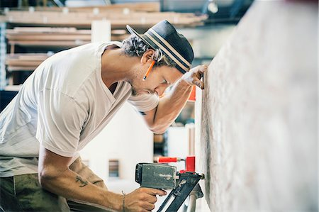 small business - Side view of carpenter working on wooden plank at workshop Stock Photo - Premium Royalty-Free, Code: 698-08226725