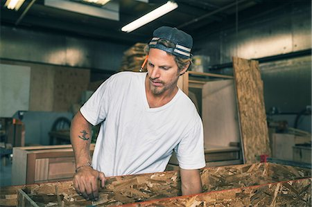 Carpenter holding wooden plank at workshop Stock Photo - Premium Royalty-Free, Code: 698-08226723